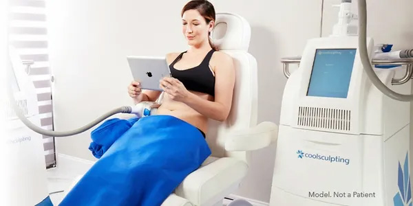 Woman sitting with iPad having CoolSculpting treatment done